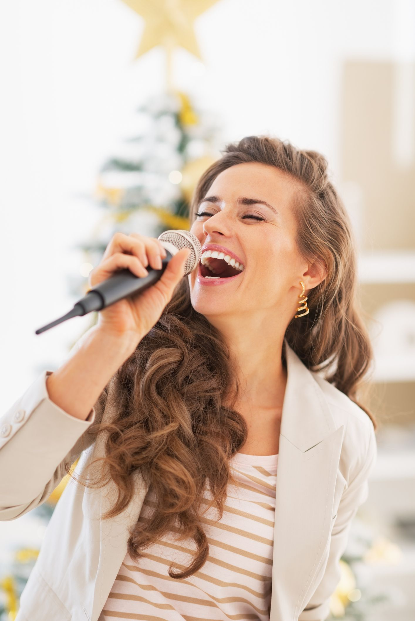 happy young woman singing in front of christmas tree