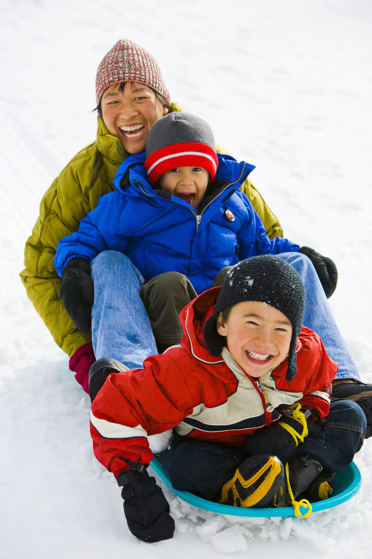 mother and two son 4 6 sledding down hill, laughing, elevated view